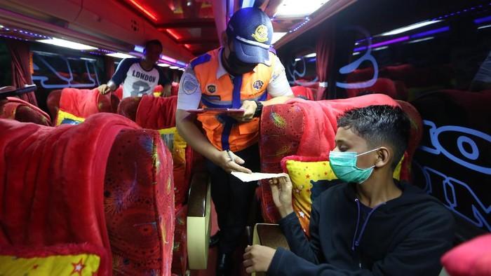 Petugas Kementerian Perhubungan memeriksa surat kelengkapan penumpang bus Antar Kota Antar Provinsi (AKAP) Terbatas di terminal tipe A Batoh, Banda Aceh, Aceh, Kamis (6/5/2021). Suasana terminal bus AKAP yang malayani transportasi dengan tujuan berbagai provinsi di pulau Sumatera dan Jawa terpantau sepi terkait adanya pemberlakuan larangan mudik Hari Raya Idul Fitri 1442 Hijriah pada 6-17 Mei 2021. ANTARA FOTO / Irwansyah Putra/foc.