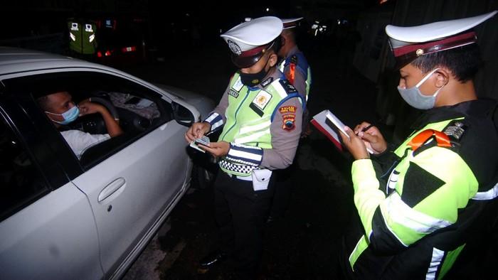 Personel kepolisian memeriksa surat kendaraan dan KTP saat penyekatan pemudik di jalur Pantura, Tegal, Kamis (6/5/2021). Menurut Satlantas Polres Tegal Kota, penyekatan mudik untuk kendaraan yang melintas di jalur Pantura dari Jakarta menuju Jawa Tengah diprediksi terjadi pada H-3 Lebaran. ANTARA FOTO/Oky Lukmansyah/rwa.