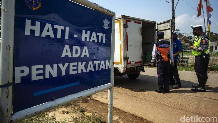 Polisi melakukan penyekatan di jalur tikus di Bekasi menuju Karawang. Pada hari kedua larangan mudik ini, puluhan kendaraan diputar balik polisi.