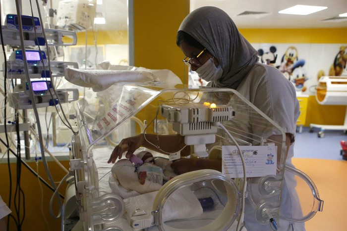 A Moroccan nurse takes care of one of the nine babies protected in an incubator at the maternity ward of the private clinic of Ain Borja in Casablanca, Morocco, Wednesday, May 5, 2021. A Malian woman gave birth to nine babies after n  to have waited only seven, announced Wednesday the Ministry of Health of Mali. . Halima CissÈ, 25, gave birth by caesarean section Tuesday in Morocco after being sent there for special care, the ministry said. (AP Photo / Abdeljalil Bounhar)