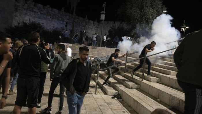 Palestinians react to stun grenades fired by Israeli police to clear the Damascus Gate to the Old City of Jerusalem after clashes at the Al-Aqsa Mosque compound, Friday, May 7, 2021. Palestinian worshippers clashed with Israeli police late Friday at the holy site sacred to Muslims and Jews, in an escalation of weeks of violence in Jerusalem that has reverberated across the region. (AP Photo/Maya Alleruzzo)