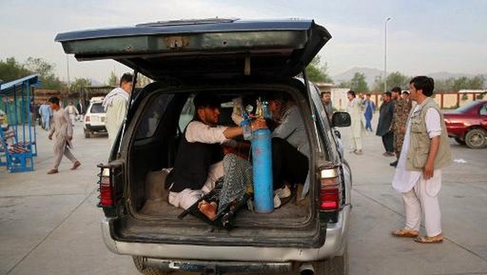 An injured man is being brought in a car to a hospital following a blast outside a school in the west Kabul district of Dasht-e-Barchi on May 8, 2021, that killed at least 25 people and wounded scores more including students, officials said. (Photo by ZAKERIA HASHIMI / AFP)