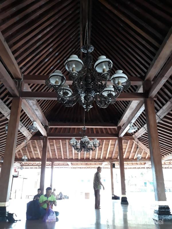 Serambi masjid yang ditopang tiang kayu jati dan berhias lampu gantung klasik