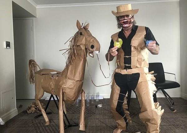 Inilah David Marriott yang menciptakan kostum koboi dan kuda kertas selama menjalani karantina COVID-19. Marriott membuat kreasi ini karena bosan menjalani karantina di sebuah kamar hotel di Brisbane, Australia. (AP)