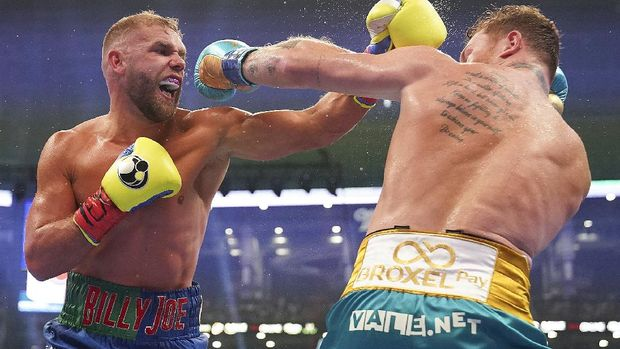 Billy Joe Saunders, left, exchanges punches with Canelo Alvarez during a unified super middleweight world championship boxing match, Saturday, May 8, 2021, in Arlington, Texas. (AP Photo/Jeffrey McWhorter)