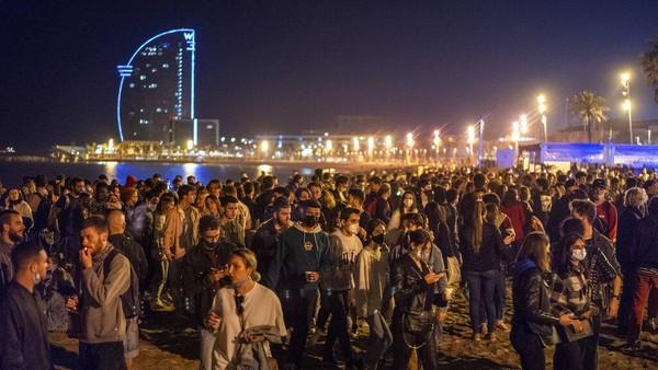 Mereka datang ke pantai itu untuk merayakan berakhirnya penerapan aturan jam malam di Spanyol.