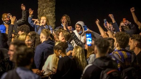 Sejumlah warga berpesta dan bersuka cita di pantai Barcelona pada Minggu (9/5/2021) dini hari.