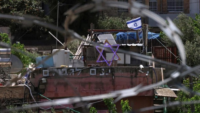 The Star of David and an Israeli flag are seen on top of a house in the Sheikh Jarrah neighbourhood of occupied east Jerusalem on May 5, 2021. - Israeli Jews backed by courts have taken over houses in Sheikh Jarrah in east Jerusalem on the grounds that Jewish families lived there before fleeing in Israels 1948 war for independence. The claimants seek to evict a total of 58 more Palestinians, according to the watchdog group Peace Now, and  Israels Supreme Court is set to announce a decision for four of those families on May 6, 2021. (Photo by Emmanuel DUNAND / AFP)