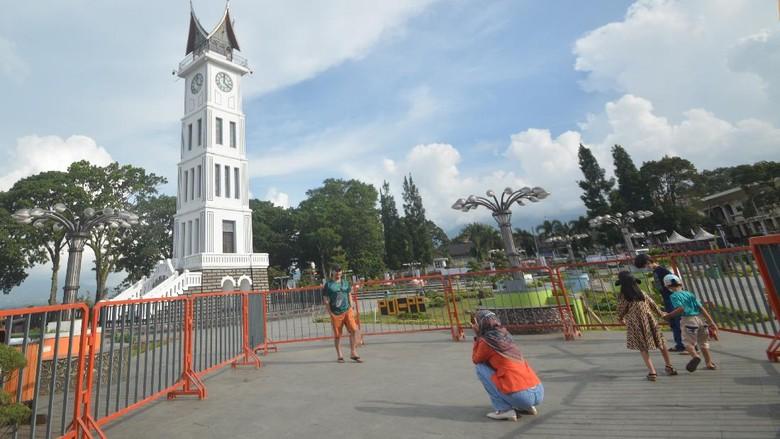 Pengunjung berfoto di pelataran Jam Gadang yang ditutup dengan pagar, di Bukittinggi, Sumatera Barat, Minggu (9/5/2021). Kapolda Sumbar Irjen Pol Toni Harmanto memastikan seluruh objek wisata di provinsi itu ditutup saat libur Idul Fitri 1442 hijriah untuk mencegah penyebaran virus COVID-19. ANTARA FOTO/Iggoy el Fitra/hp.