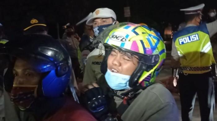 Seorang penumpang motor menangis saat disetop polisi di Kedungwaringin, meminta diberi jalan pulang karena keluarganya meninggal, Senin (10/5/2021).
