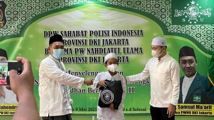 Ahmad Rifai bersama Ketua DPW SPI (Sahabat Polisi DKI Jaya) Fauzi Mahendra (baju putih) memberikan santunan kepada anak yatim di PWNU DKI Jakarta, Jakarta Timur, Minggu (9/5/2021).