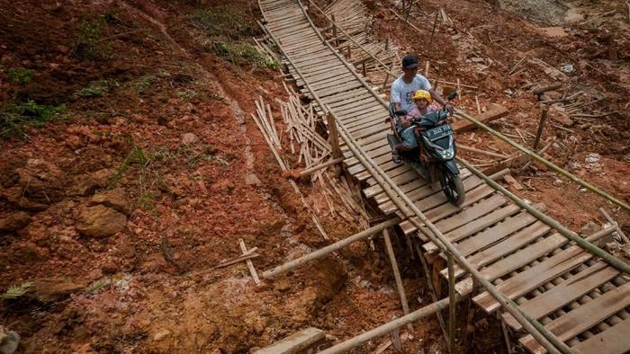 Warga melintasi jembatan yang dibangun secara swadaya di Desa Citorek Kidul, Lebak, Banten, Senin (10/5/2021). Warga setempat mengeluhkan jalan penghubung antardesa Citorek Kidul dan Citorek Tengah tersebut sering terjadi longsor ketika hujan deras dan belum dibangun sehingga mengganggu aktivitas warga. ANTARA FOTO/Muhammad Bagus Khoirunas/aww.