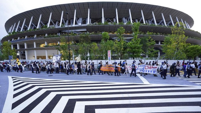 People who are against the Tokyo 2020 Olympics set to open in July, march around Tokyo's National Stadium, back, during an anti-Olympics demonstration Sunday, May 9, 2021. (AP Photo/Eugene Hoshiko)