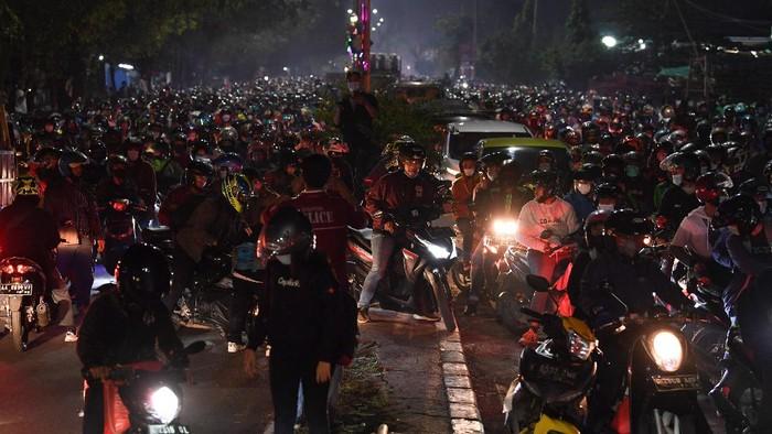 Seorang pemudik yang menggunakan sepeda motor menyiapkan surat jalan saat terjebak kemacetan di posko penyekatan mudik Kedungwaringin, Kabupaten Bekasi, Jawa Barat, Senin (10/5/2021). Polda Metro Jaya menambah jumlah petugas guna mengecek ribuan pemudik yang melintasi pos penyekatan perbatasan Bekasi -Karawang, Jawa Barat. ANTARA FOTO/Wahyu Putro A/aww.