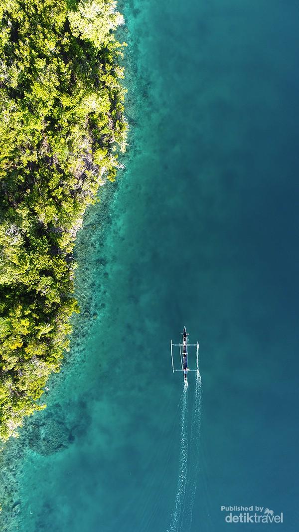 Kapal nelayan melintasi salah satu pulau di Togean. Kawasan ini masuk ke dalam perlindungan Taman Nasional Kepulauan Togean, karena memiliki keindahan terumbu karang dan biota laut yang patut untuk dilestarikan.