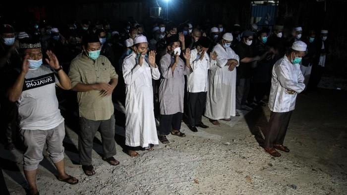 Sejumlah anggota keluarga dan kerabat berdoa bersama usai menshalatkan jenazah Ustadz Tengku Zulkarnain yang meninggal dunia akibat COVID-19 di halaman samping RS Tabrani Pekanbaru, Riau, Senin (10/5/2021) malam. Ustadz Tengku Zulkarnain meninggal dunia pada Senin (10/5/2021) akibat COVID-19 dan akan dimakamkan di pemakaman khusus COVID-19 di Palas, Rumbai. ANTARA FOTO/Rony Muharrman/aww.