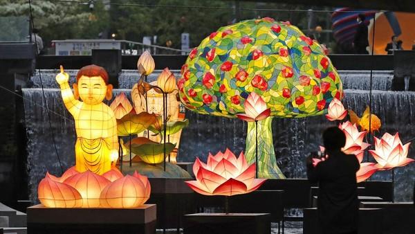 Pengunjung berjalan di dekat lentera yang ditampilkan untuk perayaan ulang tahun Buddha di ruang publik Seoul, Korea Selatan, Senin (10/5/2021).