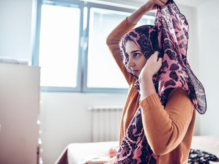 Malaysian woman with hijab in restroom, fixing make up and hijab