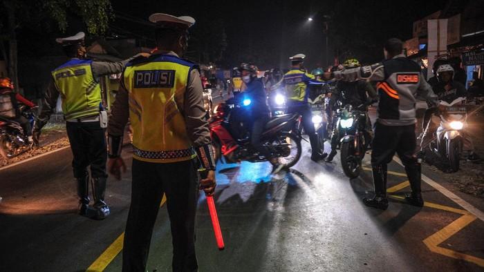 Petugas Kepolisian memutarbalikan kendaraan roda dua di posko penyakatan mudik Limbangan, Kabupaten Garut, Jawa Barat, Selasa (11/5/2021). Pada H-2 Idul Fitri 1442 H, petugas di posko penyekatan mudik Limbangan memutarbalikan ratusan pengendara roda dua yang hendak mudik ke arah Tasikmalaya, Ciamis dan Jawa Tengah. ANTARA FOTO/Raisan Al Farisi/foc.
