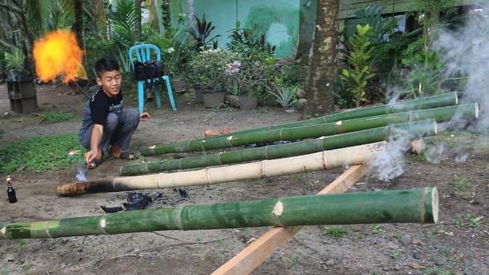 Sejumlah pemuda menyalakan beude trieng (meriam bambu) di Desa Alue Raya, Samatiga, Aceh Barat, Aceh, Rabu (12/5/2021). Memainkan meriam bambu telah menjadi tradisi yang dilakukan pemuda sebagai bentuk ekspresi kebahagiaan menyambut malam lebaran dan hari kemenangan setelah melaksanakan ibadah puasa. ANTARA FOTO/Syifa Yulinnas/foc.