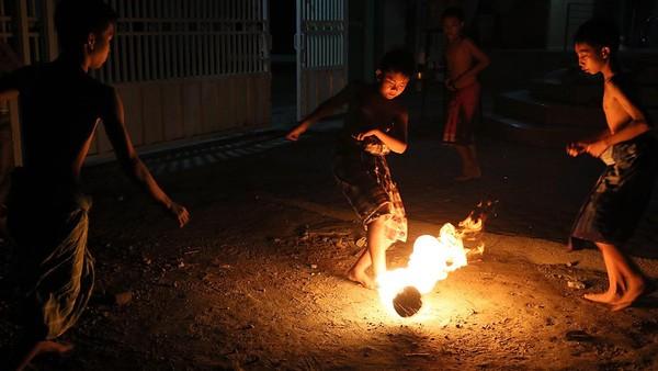 Sejumlah remaja masjid bermain sepakbola api di halaman Masjid Batul Fatah Gedog, Blitar, Jawa Timur, Selasa (11/5/2021).