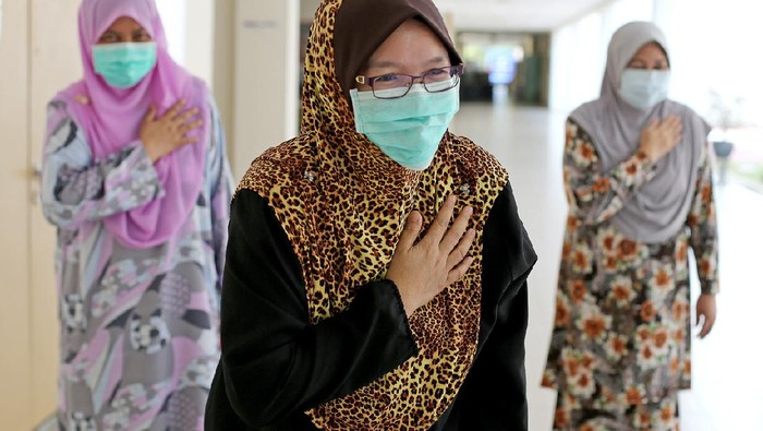 A small group of female adults placed their right palm on left chest (Malaysian culture way greetings) as an alternative to handshakes during partial lockdown in Malaysia.