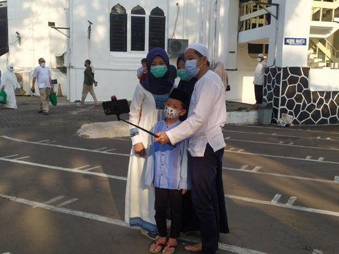 Jemaah bersama keluarganya mengabadikan momen Idul Fitiri 1442 H usai salat Id di Masjid Cut Meutia