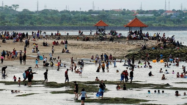 Para wisatawan bermain di sepanjang pantai.