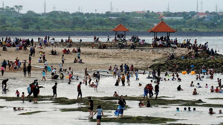 Wisatawan menikmati suasana liburan di Pantai Sanur, Denpasar, Bali, Kamis (13/5/2021). Obyek wisata yang dicanangkan sebagai kawasan zona hijau tersebut ramai dikunjungi wisatawan lokal pada liburan Idul Fitri 1442 Hijriah. ANTARA FOTO/Nyoman Hendra Wibowo/rwa.