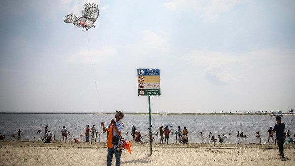 Pedagang menerbangkan layang-layang di Pantai Carnaval Ancol Jakarta, Jumat (14/5/2021).