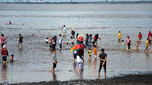 Sejumlah warga berwisata pada hari kedua Lebaran di Pantai Koneng Dumai, Riau, Jumat (14/5/2021). Obyek wisata pantai Dumai ramai dikunjungi warga pada hari kedua Lebaran yang datang dari luar daerah seperti Bengkalis, Rokan Hilir dan Pekanbaru meskipun ada larangan membuka tempat wisata oleh Polda Riau. ANTARA FOTO/Aswaddy Hamid.