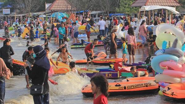 Pengunjung menikmati suasana liburan di pantai Karangsong, Indramayu, Jawa Barat, Jumat (14/5/2021). Obyek wisata pantai Karangsong ramai dikunjungi warga pada hari kedua Lebaran meskipun ada larangan membuka tempat wisata oleh Pemda setempat. ANTARA FOTO/Dedhez Anggara.