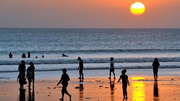 Wisatawan menikmati suasana senja di Pantai Kuta, Badung, Bali, Jumat (14/5/2021). Salah satu destinasi wisata utama di Pulau Dewata tersebut dipadati oleh ribuan wisatawan lokal selama masa liburan Hari Raya Idul Fitri 1442 Hijriah. ANTARA FOTO/Fikri Yusuf.