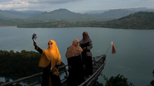 Sejumlah pengunjung berswafoto di objek wisata alam Bukit Bollangi di Kabupaten Gowa, Sulawesi Selatan, Jumat (14/5/2021). Objek wisata tersebut ramai dikunjungi wisatawan lokal saat libur lebaran Idul Fitri 1442 H. ANTARA FOTO/Arnas Padda.