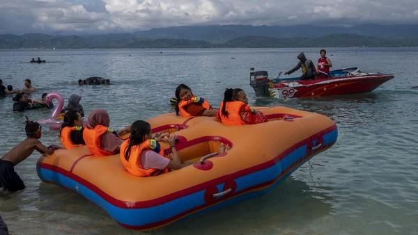 Sejumlah pengunjung menikmati wahana permainan air saat berekreasi di Pantai Wisata Tanjung Karang, Donggala, Sulawesi Tengah, Jumat (14/5/2021). ANTARAFOTO/Basri Marzuki