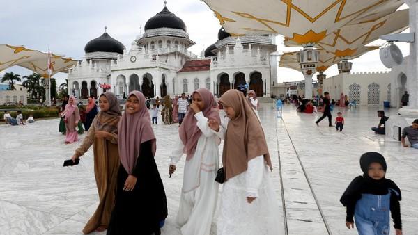 Warga memadati Masjid Raya Baiturrahman yang telah menjadi salah satu tempat wisata religi di Banda Aceh, Aceh, Jumat (14/5/2021). Pemerintah dan pengurus Masjid Raya Baiturrahman telah mengimbau pengunjung untuk mematuhi protokol kesehatan pencegahan penularan COVID-19 namun masih banyak pengunjung yang mengabaikan imbauan tersebut. ANTARA FOTO/Irwansyah Putra.