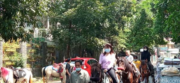 Ekspresipenunggang kuda begitu lucu.Ada yang serius ada juga yang terlihat riang saat kuda yang ditunggangi mendekati keluarga yang duduk di tepi jalan.