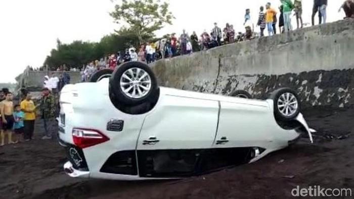 Sebuah mobil wisatawan di Banyuwangi nyungsep hingga terbalik di pinggir Pantai Blimbingsari. Sebelum nyungsep, mobil tersebut menabrak dua motor yang parkir.