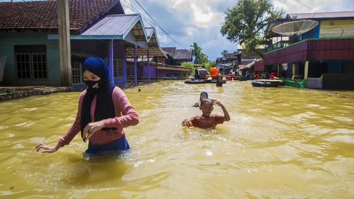 Warga bertahan di rumahnya saat banjir merendam permukiman di Jalan Biduri, Kecamatan Satui, Kabupaten Tanah Bumbu, Kalimantan Selatan, Sabtu (15/5/2021). BPBD Kabupaten Tanah Bumbu mencatat sebanyak 2.126 unit rumah di Kecamatan Satui tersebut terendam banjir setinggi 50 cm hingga dua meter akibat tingginya intensitas curah hujan yang mengakibatkan meluapnya Sungai Satui. ANTARA FOTO/Bayu Pratama S/wsj.