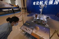 A visitor to an exhibition on Chinas space program looks at a life size model of the Chinese Mars rover Zhurong, named after the Chinese god of fire, at the National Museum in Beijing on Thursday, May 6, 2021. China has landed a spacecraft on Mars for the first time in the latest advance for its space program. The official Xinhua News Agency said Saturday, May 15, that the lander had touched down, citing the China National Space Administration. Chinese characters read: Build a Space Power. (AP Photo/Ng Han Guan)