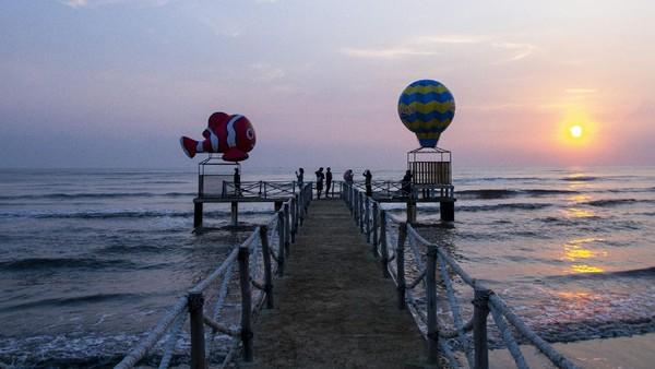 Wisatawan berswafoto sambil menikmati matahari terbit di Pantai Tanjung Pakis.