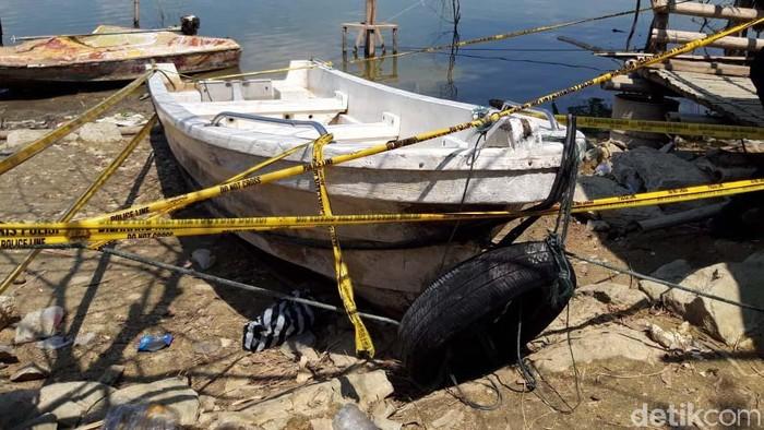 Perahu wisata pengangkut 20 orang yang terbalik di Waduk Kedungombo (WKO) Boyolali saat ini ditambatkan di pinggir waduk. Perahu itu dipasangi garis polisi.