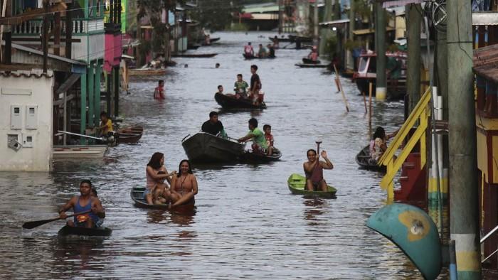 Residents navigate flooded streets in Anama, Amazonas state, Brazil (AP Photo/Edmar Barros)
