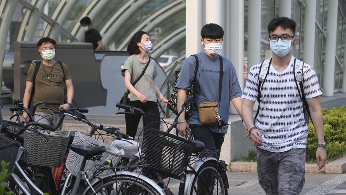 People wear face masks to protect against the spread of the coronavirus after the COVID-19 alert raise to level 3 in Taipei, Taiwan, Saturday, May 15, 2021. Taiwan, which has had enviable success in containing COVID-19, imposed new restrictions in its capital city on Saturday as it battled its worst outbreak since the pandemic began. (AP Photo/Chiang Ying-ying)