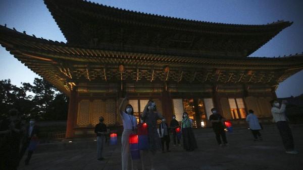 Pengunjung yang memegang lentera tradisional Korea berjalan-jalan di Istana Changdeokgung di Jongno-gu, Seoul, Korea Selatan. Istana Changdeokgung ini merupakan satu dari lima istana kerajaan era Joseon. Changdeokgung dibangun tahun 1405 oleh Raja Taejong.