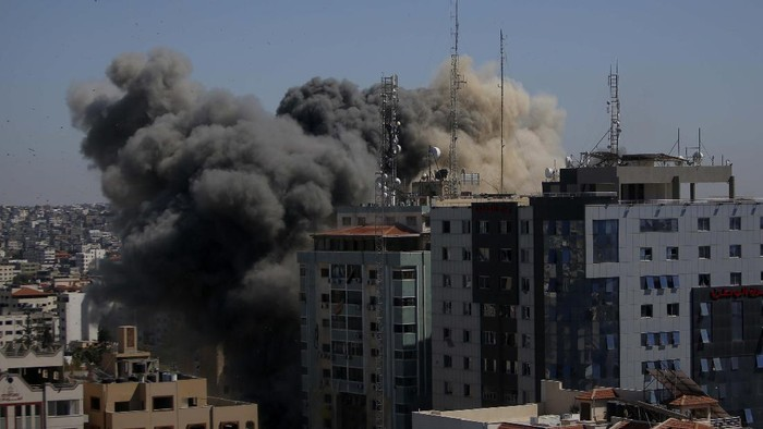 Smoke billows from a building housing various international media, including The Associated Press, after an Israeli airstrike on Saturday, May 15, 2021 in Gaza City.  The attack came roughly an hour after the Israeli military ordered people to evacuate the building, which also housed Al-Jazeera and a number of offices and apartments. There was no immediate explanation for why the building was targeted.  (Mahmud Hams /Pool Photo via AP)