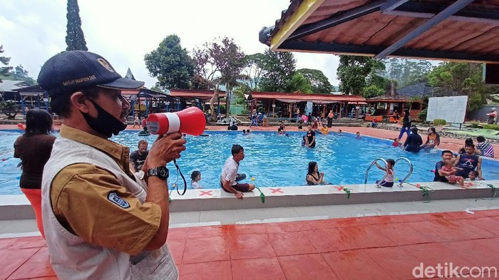 Petugas mengingatkan pengunjung di objek wisata Ciwidey untuk mematuhi protokol kesehatan