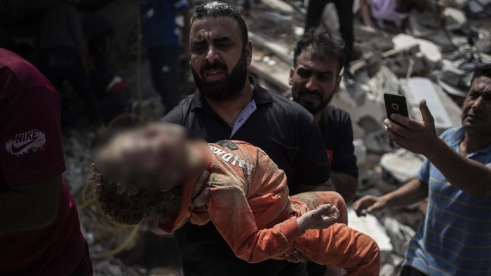 A Palestinian man carries a girl who was rescued from under the rubble of a destroyed residential building following deadly Israeli airstrikes in Gaza City, Sunday, May 16, 2021. The airstrikes flattened three buildings and killed at least 26 people Sunday, medics said, making it the deadliest single attack since heavy fighting broke out between Israel and the territory's militant Hamas rulers nearly a week ago. (AP Photo/Khalil Hamra)