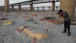 Polisi tengah berjaga di samping jenazah yang dikuburkan di tepi sungai Gangga, India. Diperkirakan ada ratusan jenazah yang terkubur di area tersebut.
