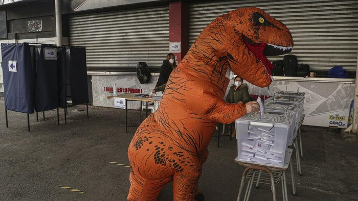 Chile gelar pemilihan Konvensi Konstitusional akhir pekan lalu. Di tengah penyelenggaran pemilihan, seorang warga berkostum dinosaurus curi perhatian publik.